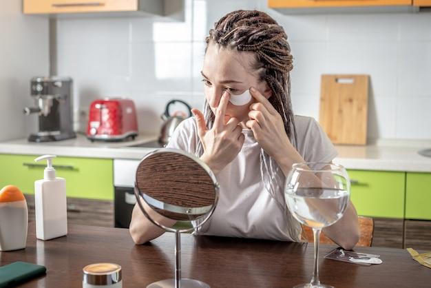 Молодая современная женщина наклеивает патчи для кожи вокруг глаз дома