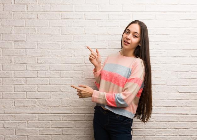 指で横を指している若い現代女性