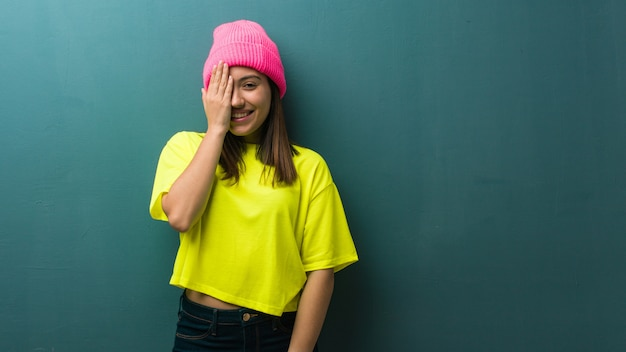 Young modern woman shouting happy and covering face with hand