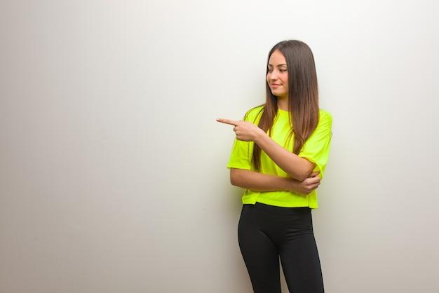 笑顔で横を指している若い現代女性