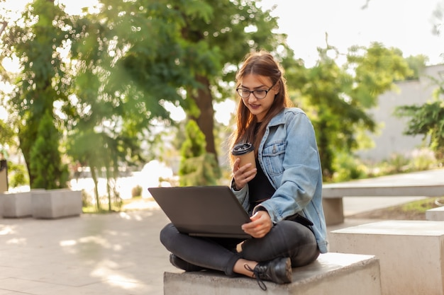 Young modern woman student in a denim jacket sitting at park and looks at the laptop screen with coffee cup on hand. distance learning. modern youth concept.