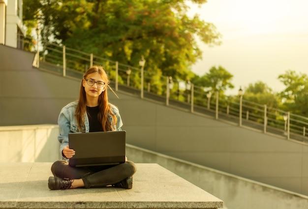 Студент молодой современной женщины в джинсовой куртке, сидя на лестнице с ноутбуком. дистанционное обучение. современная молодежная концепция.