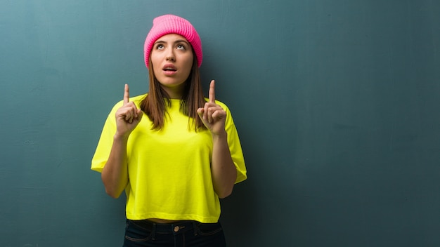 Young modern woman surprised pointing up to show something