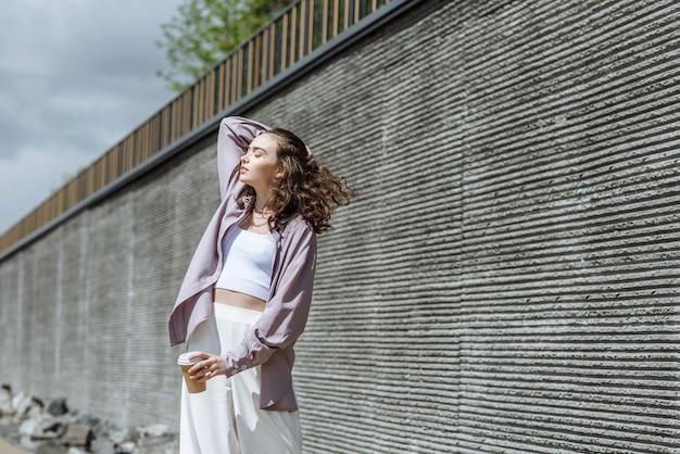 벽 배경에 여름에 커피와 함께 젊은 현대 여성