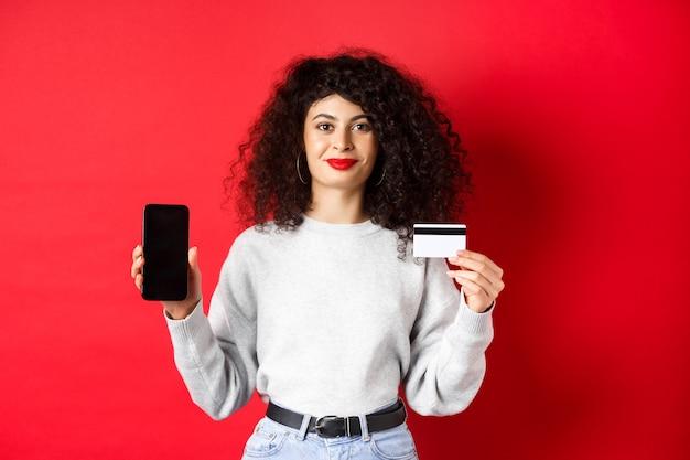곱슬머리를 한 젊은 현대 여성이 플라스틱 신용 카드와 휴대 전화 화면을 보여주고 온라인 쇼핑 앱을 보여주고 빨간색 배경에 서 있습니다.