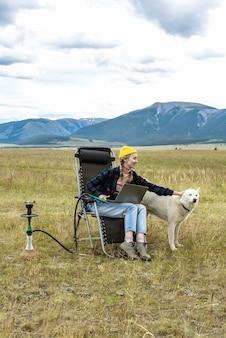 젊은 현대 여성은 컴퓨터에서 일하고 개를 쓰다듬고 산에서 물담배를 피웁니다. 라이프 스타일 및 여행 개념