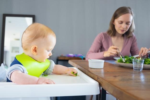 緑の野菜を食べる若いお母さんとかわいい赤ちゃんの娘