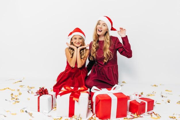 Молодая мама и дочь в шляпах санты веселятся с рождественскими подарками