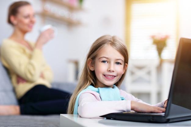 Молодая мама и ее маленькая дочь сидят на диване у себя дома за ноутбуком