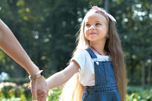 젊은 엄마와 긴 머리를 가진 그녀의 작은 딸이 여름 공원에서 손을 잡고 함께 걷고 있습니다.
