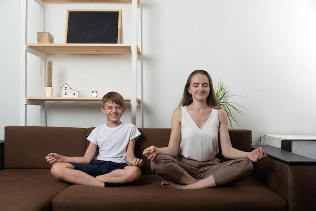 Молодая мама и сын занимаются йогой дома. мама и ребенок сидят в позе лотоса и медитируют.