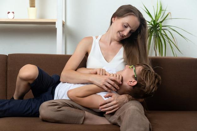 Молодая мама и сын-подросток болтают, сидя на диване.