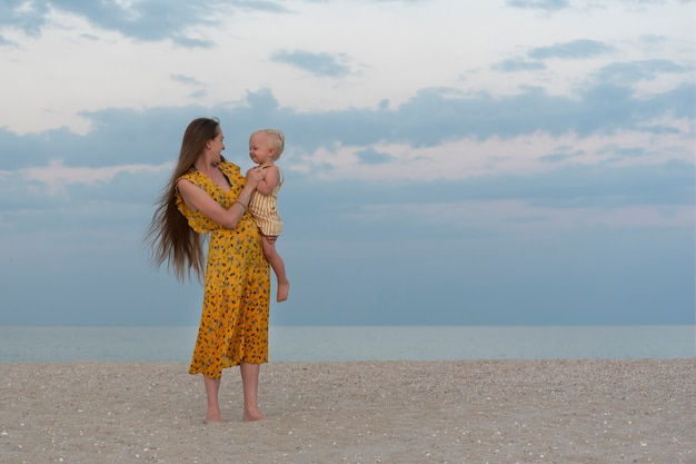 Young mom in bright yellow sundress and long hair holds baby. portrait of mother with baby on sea background.