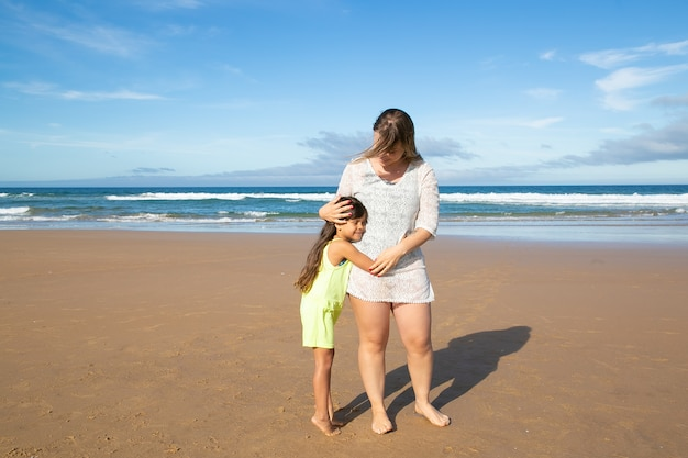 Young mom and cute black haired girl hugging while standing on ocean beach