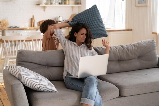 젊은 엄마 거리 학생 또는 프리랜서 작업자가 집에서 일하고 작은 아이가 노트북에서 산만합니다.