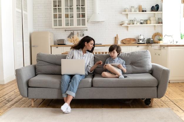 若いお母さんは、タブレットで息子の遊びを見ている自宅のフリーランサーの母親からのオンライン学習で息子を助けます