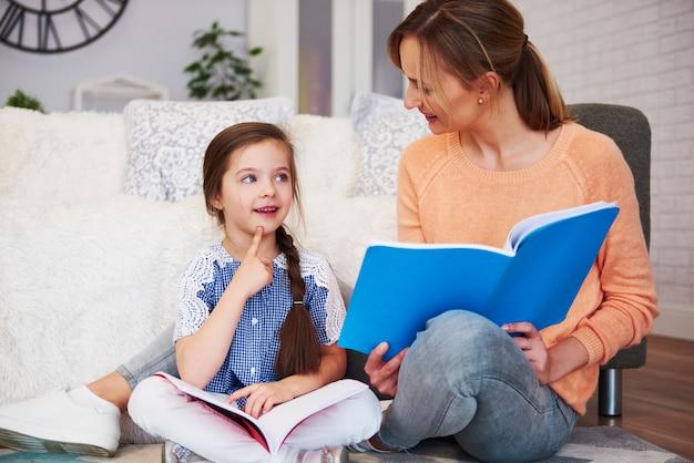 宿題で娘を助ける若いお母さん