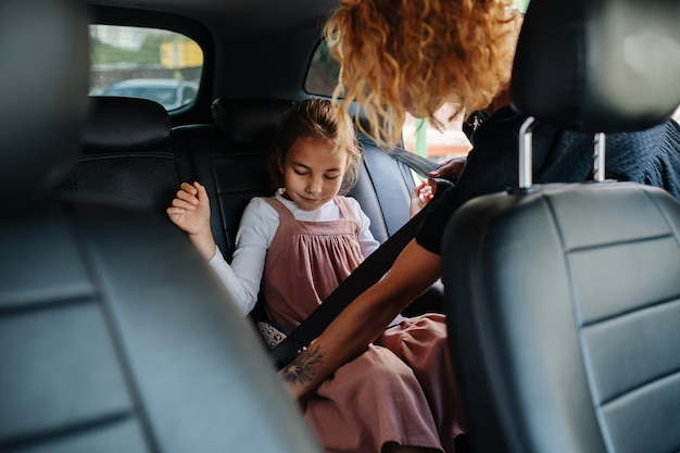 Young mom helping her eight year old daughter to fasten her back seat belt in a car. from inside a salon.