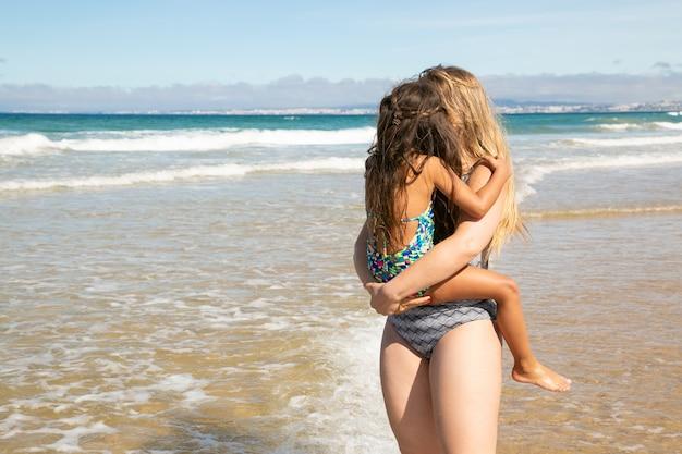 Giovane mamma che tiene la piccola figlia tra le braccia, trascorre il tempo libero con il bambino sulla spiaggia, guardando il mare