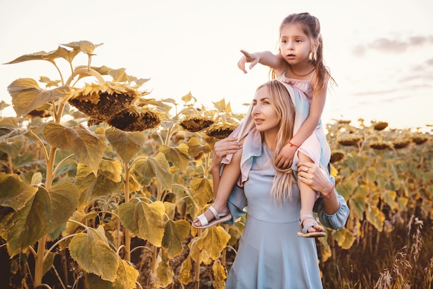 Young mom holds on shoulders her little daughter