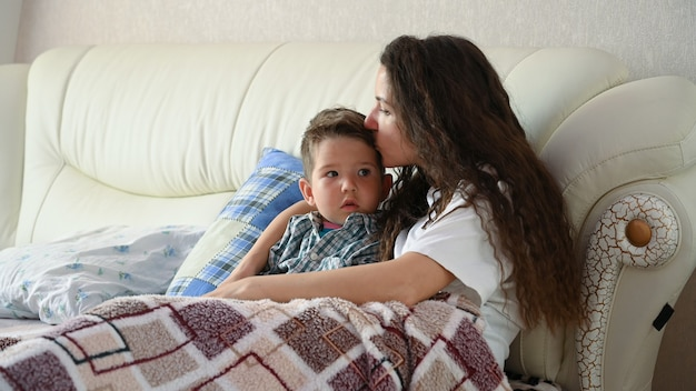 Молодая мама целует своего малыша в постели перед сном.
