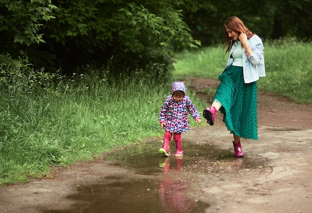 Young mom and little daughter have fun walking in gumboots on the pools in park