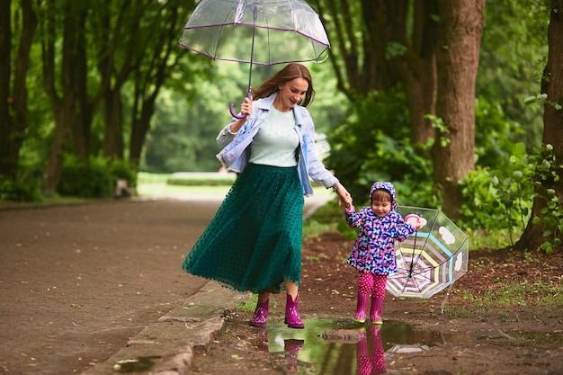 Young mom and little daugther have fun walking with umbrellas on the pools after the rain