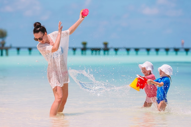 Young mom and little girls having fun during summer