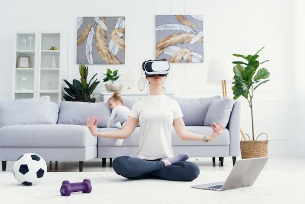 Молодая мама медитирует в позе лотоса йоги в очках vr, а ее дети играют дома