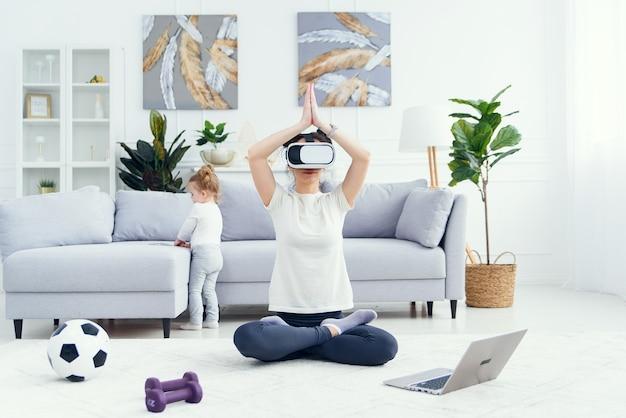 彼女の娘が漫画を見ている間、arメガネを使用して蓮華座で瞑想している若いお母さん