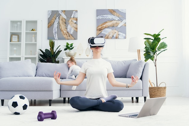 Young mom meditating in lotus yoga position at vr glasses while her children playing at home