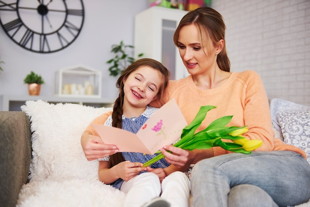 母の日にグリーティングカードと花を受け取る若いお母さん