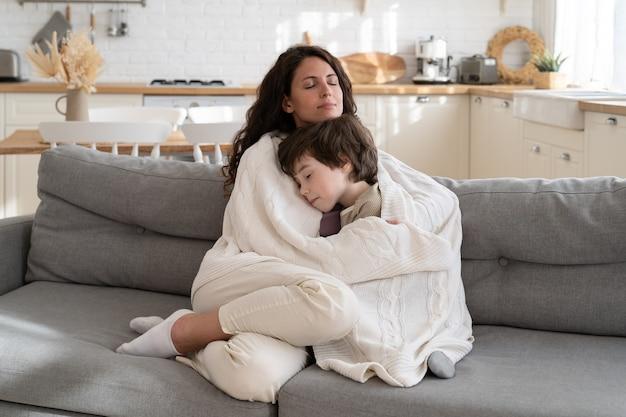 若いお母さんは居心地の良いソファに座って、自宅で週末の朝に毛布で覆われた就学前の息子とリラックスします