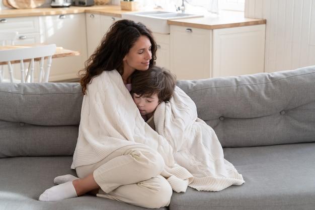 젊은 엄마는 주말 아침 집에서 담요로 덮인 취학 전 아들과 함께 아늑한 소파에 앉아 휴식을 취합니다