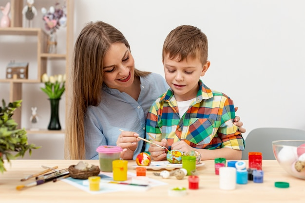 Young mom and son painting eggs for easter