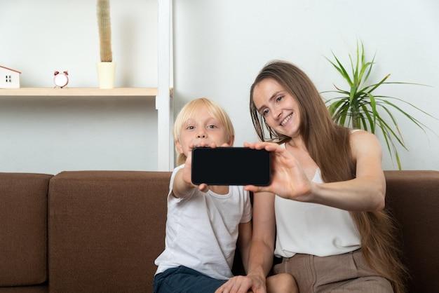 Молодая мама делает селфи с сыном. мама и ребенок показывают экран смартфона.