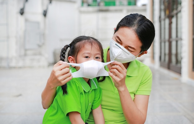 Young mom wearing protective mask for her daughter while outside to against air pollution in bangkok city