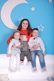 Young mom with baby boy and two little children on a white sofa. blue wall with a white moon and stars on a wall.