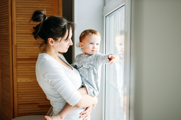 Young mom with baby girl on hands near window at home