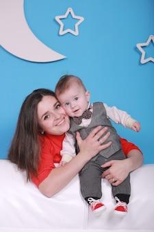 흰색 소파에 귀여운 아기와 젊은 엄마. 달과 별 벽에 파란색 벽.