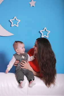 Young mom with cute baby boy on a white sofa. blue wall with a white moon and stars on a wall.