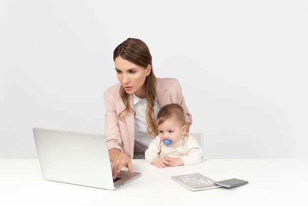 Young mom working on computer and babysitting