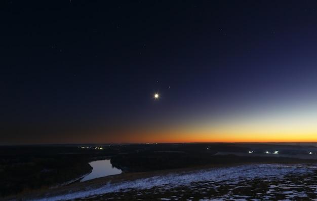 Молодая луна над рекой в сумерках. яркое вечернее небо после захода солнца.