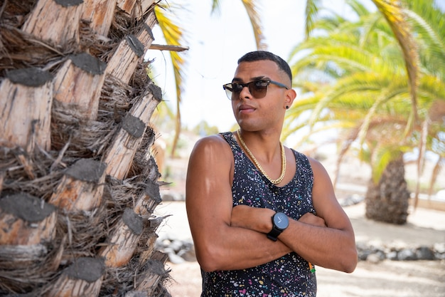 Young moroccan boy poses with folded arms and sunglasses in summer.