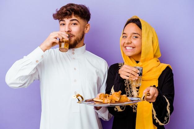 보라색 배경에 고립 된 라마단 달을 축하하는 차를 마시는 젊은 모로코 부부