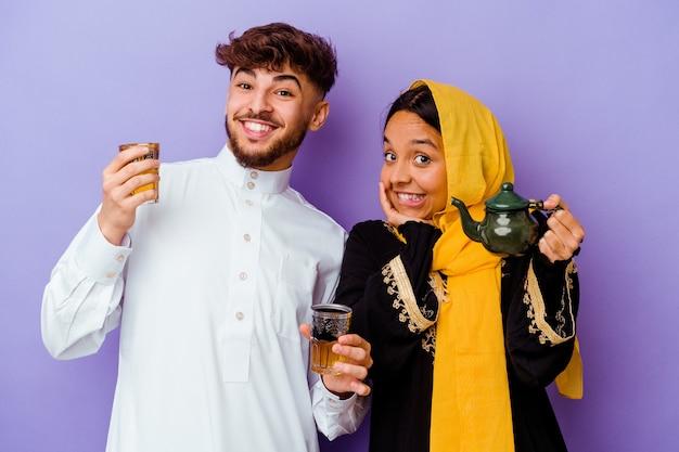 紫色の背景で隔離ラマダン月を祝うお茶を飲む若いモロッコのカップル