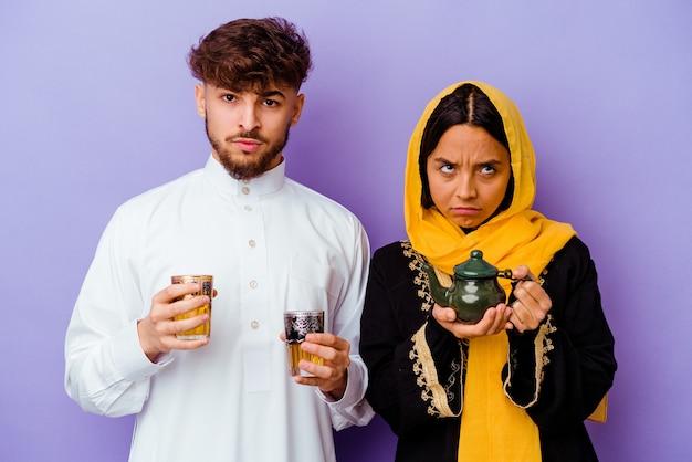 紫色の壁に分離されたラマダン月を祝うお茶を飲む若いモロッコのカップル