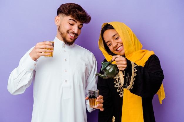 Young moroccan couple drinking tea celebrating ramadan month isolated on purple