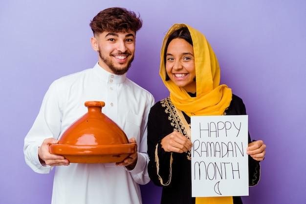 Молодая марокканская пара в типичном арабском костюме празднует рамадан, изолированную на фиолетовом