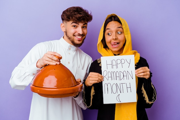 Young moroccan couple wearing a typical arabic costume celebrating ramadan isolated on purple background